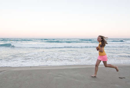 CANYAMEL, MALLORCA, BALEARIC ISLANDS, SPAIN - JULY 18, 2016: Young smiling happy brown haired girl runs barefoot speed blur on the sandy beach with ocean waves, pink sunset horizon and full moon on a summer evening on July 18, 2016 in Canyamel, Mallorca,