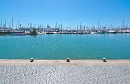 masts: PALMA DE MALLORCA, BALEARIC ISLANDS, SPAIN - APRIL 10, 2016: Quay near marina with yacht and masts and turquoise sea water on a sunny day in Palma de Mallorca, Balearic islands, Spain on April 10, 2016. Editorial