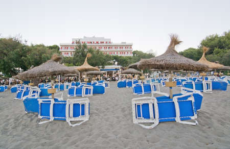 lounge chairs: CANYAMEL, MALLORCA, BALEARIC ISLANDS, SPAIN - JULY 18, 2016: Canyamel sandy beach with blue sun lounge chairs and hotel in the background on a summer evening on July 18, 2016 in Canyamel, Mallorca, Balearic islands, Spain. Editorial