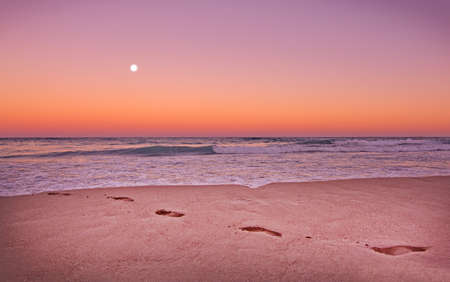 Empty sandy beach with footprints, ocean waves and full moon in expressive dusk orange and purple light in Mallorca, Balearic islands, Spain. Stock Photo