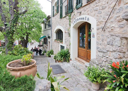VALLDEMOSSA, MALLORCA, BALEARIC ISLANDS, SPAIN - APRIL 30, 2016: Lush street and Capamunta cafe entrance in Valldemossa, Mallorca, Balearic islands, Spain on April 30, 2016.