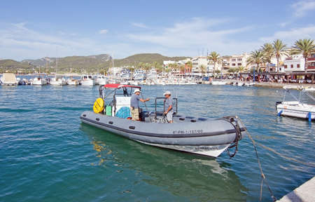onboard: PORT ANDRATX, MALLORCA, SPAIN - AUGUST 5, 2016: Two men onboard a rib boat in port on a sunny summer day in August 5 in Port Andratx, Mallorca, Spain.