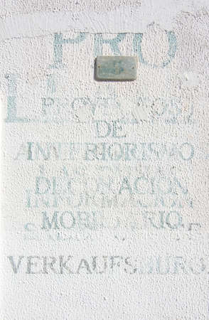 roughcast: PORT ANDRATX, MALLORCA, SPAIN - AUGUST 5, 2016: Printed unlegible words in various languages on white roughcast wall on August 5 in Port Andratx, Mallorca, Spain.