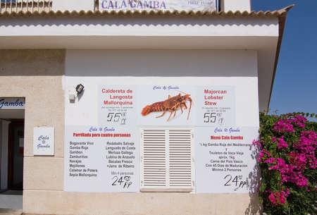 CALA GAMBA, MALLORCA, Balearen, Spanje - 30 juli 2016: Cala Gamba jachthaven visrestaurant menu aan de muur op een zonnige dag op 30 juli 2016 in Palma de Mallorca, Balearen, Spanje.