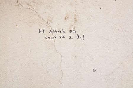 cosa: PALMA DE MALLORCA, BALEARIC ISLANDS, SPAIN - APRIL 4, 2016: Writing on a cracked stone wall, El Amor es Cosa de 2, Love is caused by 2, in Palma de Mallorca, Balearic islands, Spain on April 4, 2016.