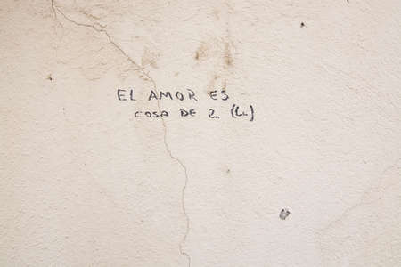 PALMA DE MALLORCA, BALEARIC ISLANDS, SPAIN - APRIL 4, 2016: Writing on a cracked stone wall, El Amor es Cosa de 2, Love is caused by 2, in Palma de Mallorca, Balearic islands, Spain on April 4, 2016.