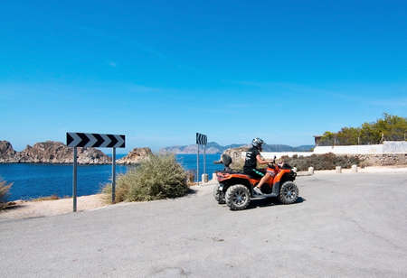 SANTA PONSA, MALLORCA, BALEARIC ISLANDS, SPAIN - SEPTEMBER 3, 2016: Man on quad motorcycle takes offnear islets of Malgrats on a sunny summer day on September 3, 2016 in Santa Ponsa, Mallorca, Balearic islands, Spain. Editorial