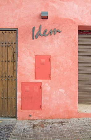 roughcast: PALMA, MALLORCA, SPAIN - AUGUST 29, 2016: Idem sign on red roughcast wall in Santa Catalina on a summer day on August 29, 2016 in Palma, Mallorca, Spain.