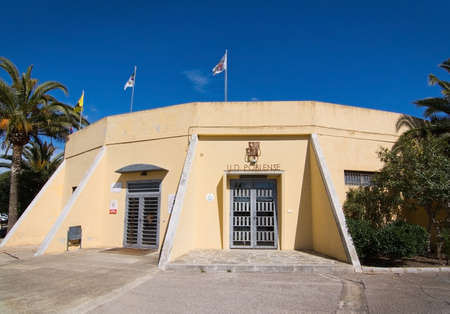 SA POBLA, MALLORCA, SPAIN - APRIL 3, 2016: CD Poblense entrance building with flags, emblems and palm trees with blue sky on April 3, 2016 in Sa Pobla, Mallorca, Balearic islands, Spain in April. Editorial