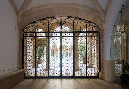 PALMA DE MALLORCA, BALEARIC ISLANDS, SPAIN - SEPTEMBER 22, 2016: Beautiful courtyard door in wrought black iron on September 22, 2016 in Palma de Mallorca, Balearic islands, Spain.