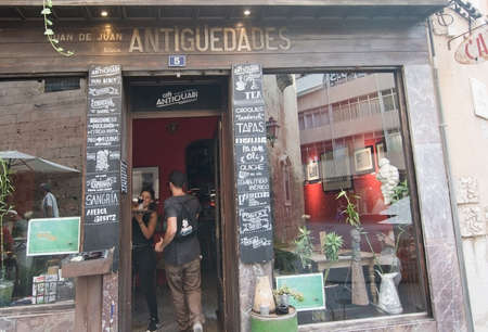 antiquary: PALMA DE MALLORCA, BALEARIC ISLANDS, SPAIN - SEPTEMBER 22, 2016: Antiquary bar Palma entrance front door meeting and interesting objects in window on September 22, 2016 in Palma de Mallorca, Balearic islands, Spain.