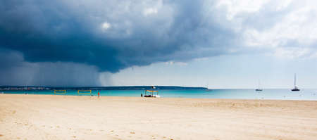 beach rain: CAN PASTILLA, MALLORCA, BALEARIC ISLANDS, SPAIN - SEPTEMBER 30, 2016: Yellow volleyball nets and players on the beach with dark cloud of thunderstorm and rain approaching on September 30, 2016 in Can Pastilla, Mallorca, Balearic islands, Spain. Editorial