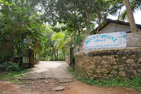 rocky point: TANGALLE, SRI LANKA, ASIA - DECEMBER 12, 2014: Sign for Rocky Point where dirt road meets asphalt on December 12, 2014 in Tangalle, Sri Lanka, Asia.