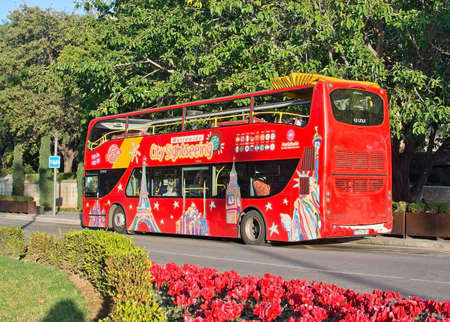 PALMA DE MALLORCA, SPAIN - DECEMBER 11, 2016: Red tourist sightseeing bus and red flowers in the city on December 11, 2016 in Palma de Mallorca, Spain.