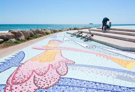 mallorca: PORTIXOLMOLINAR, MALLORCA, BALEARIC ISLANDS, SPAIN - APRIL 10, 2016: Bicyclists take a break by Molinar mosaic tower in Mallorca, Balearic islands, Spain on April 10, 2016. Editorial