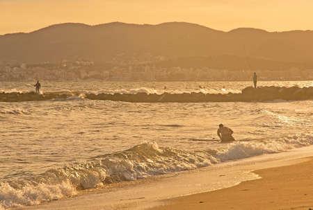 palma: PALMA DE MALLORCA, BALEARIC ISLANDS, SPAIN - JUNE 29, 2017: Surfers at Molinar beach on a sunny and windy summer evening on June 29, 2017 in Palma de Mallorca, Balearic islands, Spain.