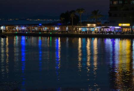 MAJORQUE, ESPAGNE - 24 juillet 2013: Scène de nuit avec des reflets de néons depuis les restaurants de la jetée de Cala Estancia. Au loin, les lumières de Magaluf le 24 juillet 2013 à Majorque, îles Baléares, Espagne. Éditoriale