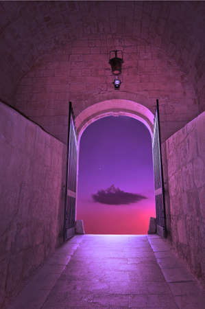 Purple cloud on pink sky with small star, through the gates of medieval fairy tale gates - concept for new dimensions, transition, dream, wishing or hope concept. Stock fotó