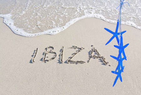 Blue starfish and Ibiza written in sand on beach with wave in Ibiza, Balearic islands, Spain