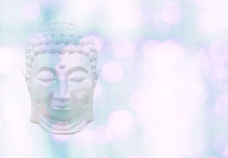 Buddha head on bokeh lights soft pink green pastel color background bokeh texture