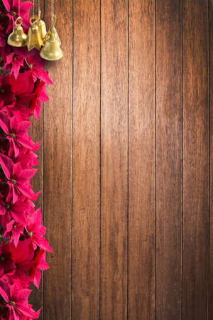 Red christmas poinsettia flower margin vertical or horizontal on shiny classy wood plank background texture surface.