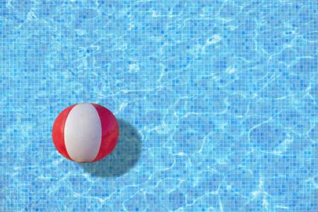 Ball in turquoise mosaic pool concept for playtime, back to work, school start for example.  Stock Photo