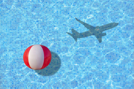 Vacation ends ball is left in pool and shadow of leaving airplane takes off concept for back to work, school start for example.  Stock Photo