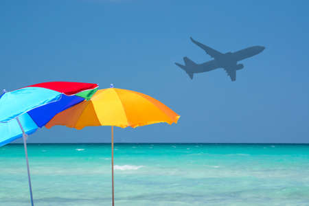 Colorful parasols and airplane turquoise water in tourist paradise tourism concept.