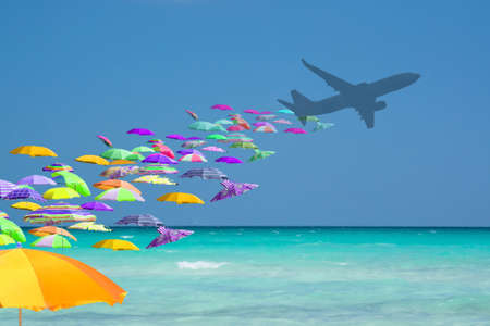 Colorful parasols tourist invasion from airplane turquoise water in tourist paradise travel playful mass tourism concept.