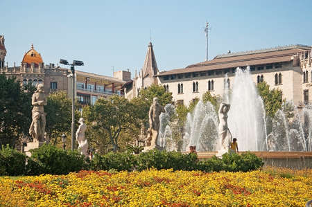 BARCELONA, SPAIN - JULY 31, 2012: View over Plaza Catalunya fountain sculptures and Hotel Barcelona building on a sunny summer day on July 31, 2012 in Barcelona, Spain.