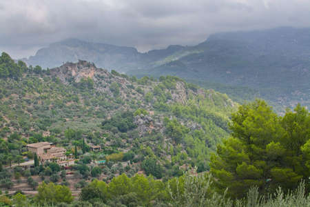Majestic mountain landscape with sun and shade and green nuances before thunderstorm in August, Mallorca, Spain.