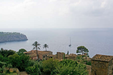 Village and sea landscape with sun and shade and green nuances before thunderstorm in August, Mallorca, Spain. Фото со стока