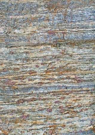 Metamorphic rock surface showing granates and bands of biotite and quartz in Haninge, Stockholm, Sweden.