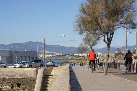 PALMA DE MALLORCA, SPAIN - DECEMBER 6, 2018: Bicyclist in red on track along the ocean on December 6, 2018 in Palma de Mallorca, Spain.
