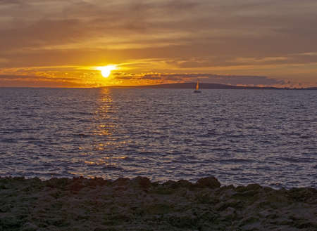 Seascape with sailboat over sunset in the Mediterranean sea in Mallorca, Spain.