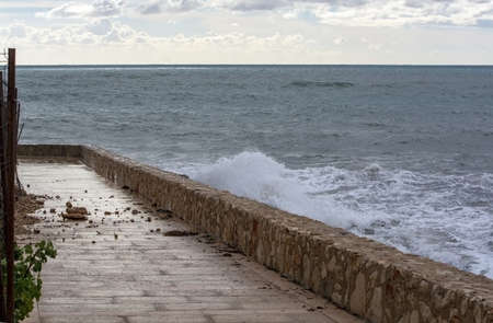 Sea water breaks against rocks and inundates promenade on a stormy winter day in Mallorca, Spain.