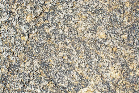 Granite surface texture closeup background shows large crystals of brown feldspar, quartz and black biotite.