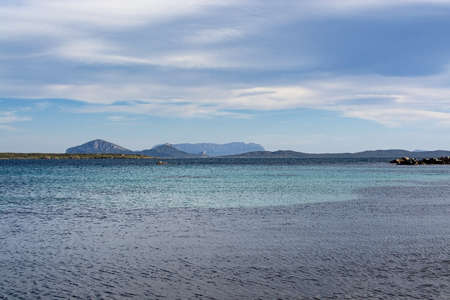 Seascape from a winter beach and blue and green sea in Costa Smeralda, Sardinia, Italy in March. Stok Fotoğraf