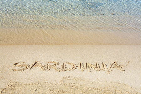 Sardinia word written in sand on a beach in Costa Smeralda, Sardinia, Italy. Stock fotó - 120294606