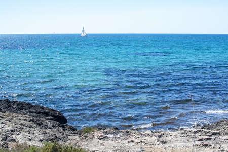 Rocky coast and sailboat on the horizon on turquoise Mediterranean sea outside Mallorca, Spain.