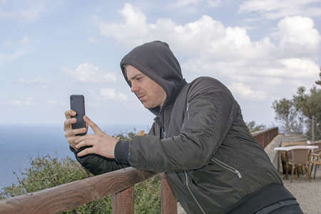 Young handsome man in black hood jacket photographs the sea takes a picture with smartphone in Mallorca, Spain Фото со стока