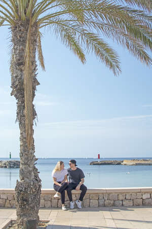 Young natural and casual sporty couple sit under palm tree by the ocean in Mallorca, Spain.