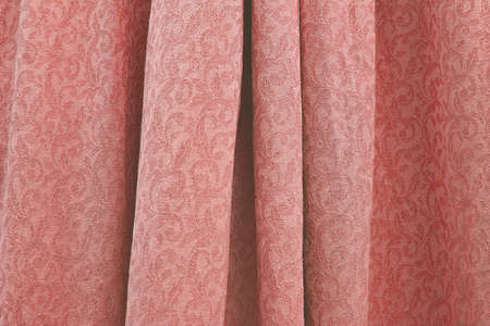 Beautiful folded damask woven cotton fabric background texture horizontal toned in trend color Living Coral.