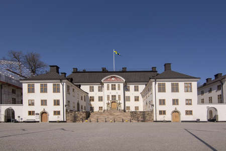 STOCKHOLM, SWEDEN - APRIL 20, 2019: Karlberg castle front with Swedish flag on a sunny day on April 20, 2019 in Stockholm, Sweden.