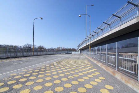 Yellow dots on wide pedestrian bridge next to car route in Stockholm, Sweden.