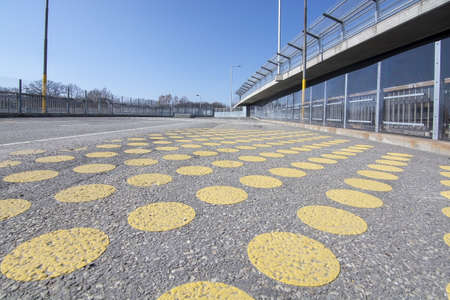 Yellow dots on wide pedestrian bridge next to car route in Stockholm, Sweden. Stock Photo - 123892602