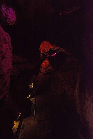 Cave interior with stalactites and stalagmites lit in colors near Porto Cristo, Mallorca, Spain. Stock Photo