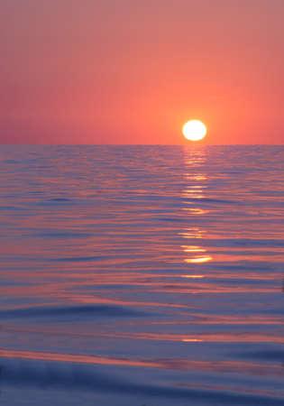 Sun rises beyond horizon on Mediterranean ocean from Mallorca, Spain. 写真素材