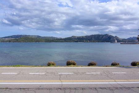 Asphalt countryroad crosses horizontal next to Mediterranean sea in Sardinia, Italy. 写真素材