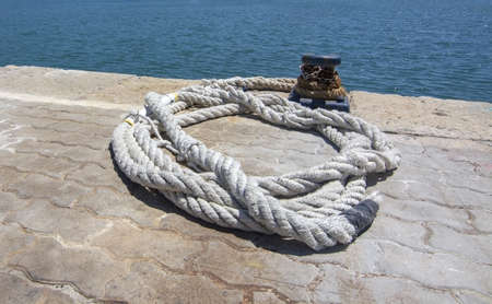 Thick white mooring rope closeup on empty mooring place on a sunny day in a harbor in Mallorca, Spain.